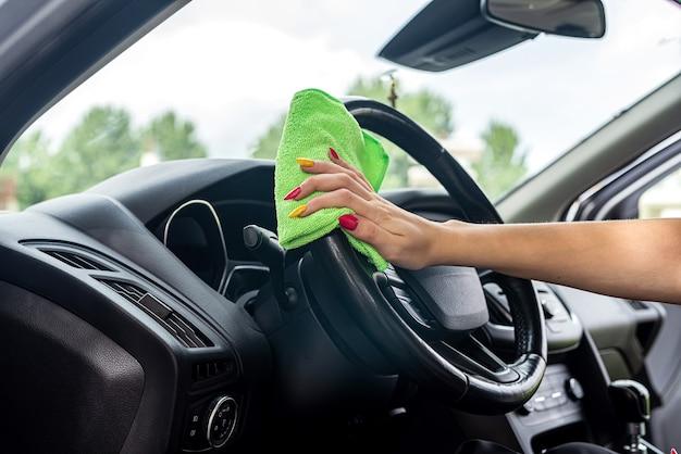 Mão com pano de microfibra verde para limpar o console do interior do carro, close-up