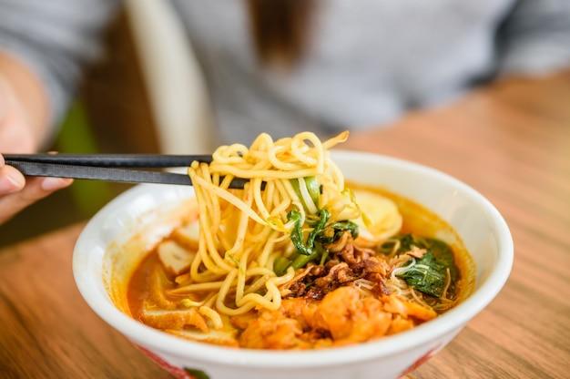 Mão com pauzinhos chineses que comem o macarronete, sopa do caril do macarronete do camarão de malásia.