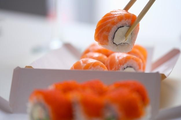 Mão com pauzinhos descartáveis segurando sushi de saquê nigiri com salmão