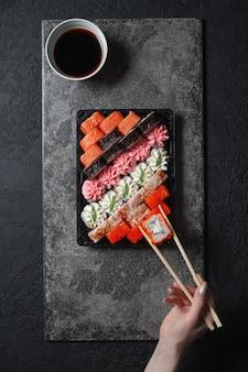 Mão com pauzinhos, restaurante japonês, prato de rolo de sushi na placa de ardósia preta. conjunto para uma pessoa, com pauzinhos, gengibre, soja, vista superior.