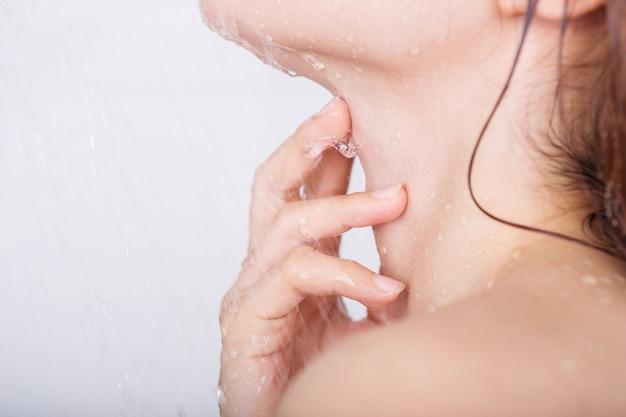Mão com pescoço de mulher que toma banho