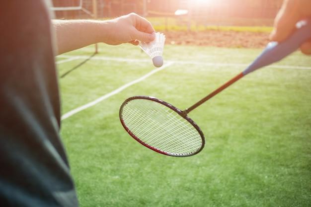 Mão com peteca na grama, uma raquete próxima.