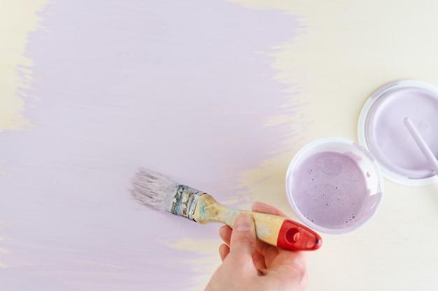 Mão com pincel e potes de tinta lilás pintando um fundo amarelo. copie o espaço. vista do topo.