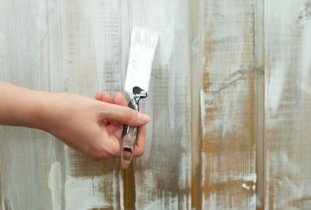 Mão com pincel pinta a parede de madeira em branco