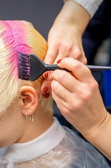 Mão com pincel tingindo o cabelo branco de uma mulher em cor de rosa no salão de cabeleireiro