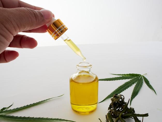 Mão com pipetas e cannabis extrair óleo.