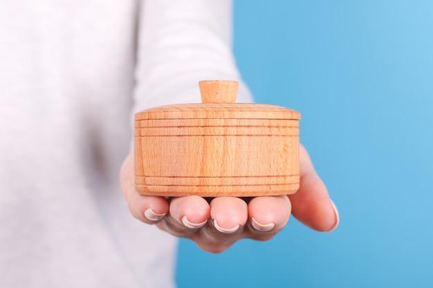 Mão com pote de madeira para sal isolado