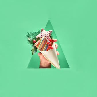 Mão com presente ecológico no cone de madeira compensada no furo triangular de papel