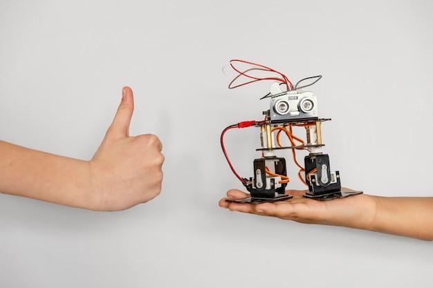 Mão com robô e sinal de ok