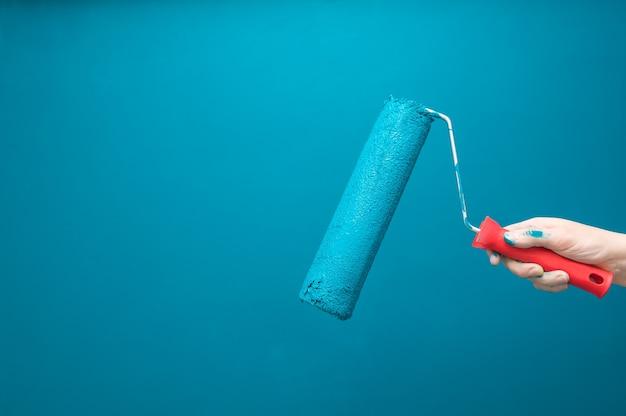 Mão com rolo de pintura em superfície pintada de azul claro