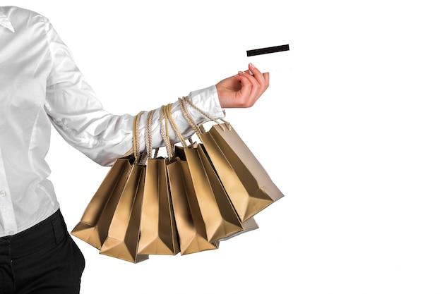 Mão com sacolas de compras e cartão de crédito