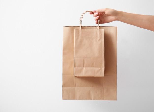 Mão com sacos de papel acesos