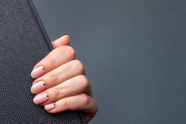 Mão com superfície de couro preto com unhas nude rosa em cinza
