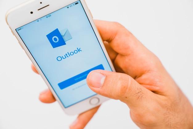 Mão com telefone e aplicativo outlook