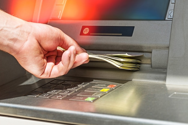 Mão com tirar dinheiro de um caixa eletrônico. caixa eletrônico do banco em papel-moeda no banco removendo moeda