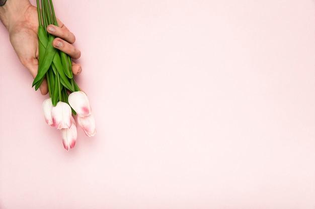 Mão com tulipas e cópia-espaço