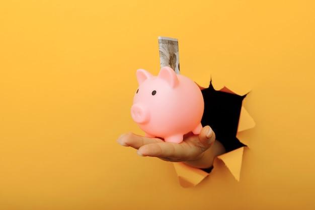 Mão com um cofrinho e uma nota de dólar através de um buraco de papel amarelo. investimento e economia.
