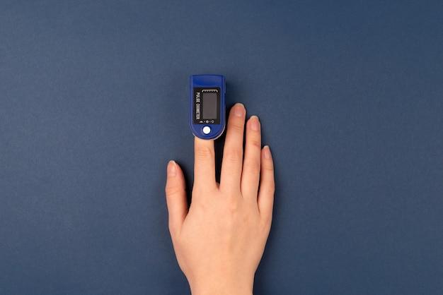 Mão com um dedo no oxímetro de pulso em fundo azul escuro. auto monitoramento e proteção durante o conceito de pandemia.