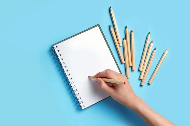 Mão com um lápis sobre um caderno nas proximidades estão lápis de cor