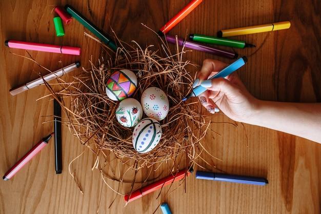 Mão com um marcador no fundo de ovos de páscoa coloridos que se encontram em um ninho em um fundo de madeira. marcadores estão espalhados por toda parte