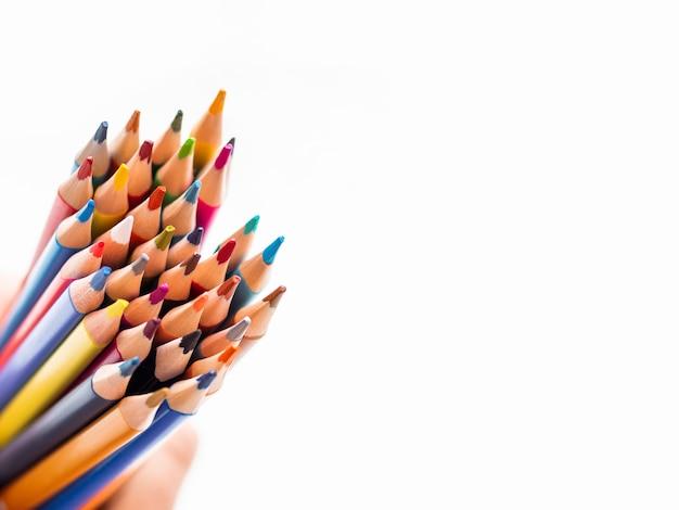 Mão com um monte de lápis coloridos sobre fundo branco