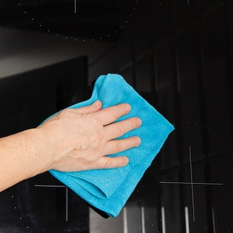 Mão com um pano de microfibra azul esfrega um fogão de cerâmica de vidro na cozinha.