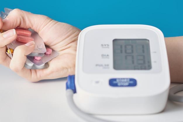Mão com um punhado de comprimidos e monitor digital de pressão arterial. conceito de cuidados de saúde e medicina