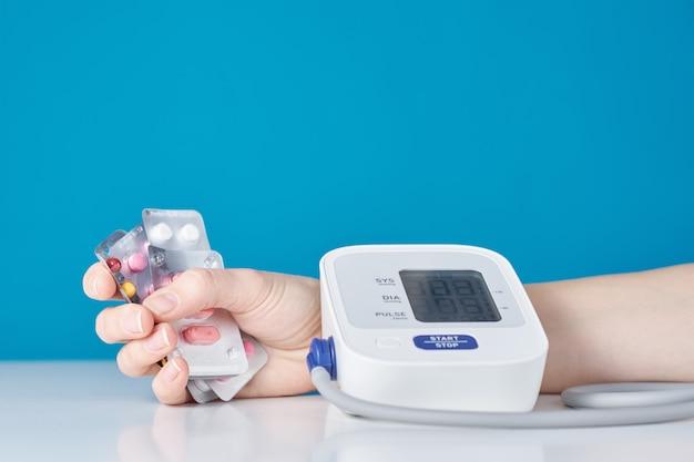 Mão com um punhado de pílulas e monitor digital de pressão arterial. conceito de cuidados de saúde e medicina