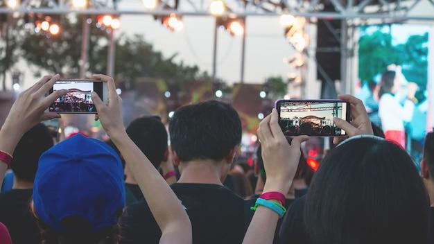 Mão com um smartphone grava festival de música ao vivo, tirando foto do palco do concerto