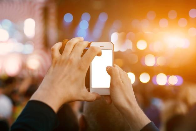 Mão com um smartphone grava festival de música ao vivo