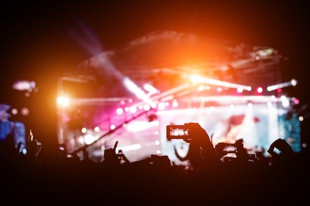 Mão com um smartphone para filmar festival de música ao vivo