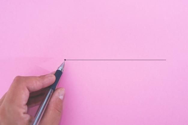 Mão com uma caneta com um contorno até o ponto final em um fundo de papel rosa. conceito de ideia de inspiração de criatividade