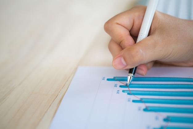 Mão com uma escrita da pena em um papel com um gráfico de barras