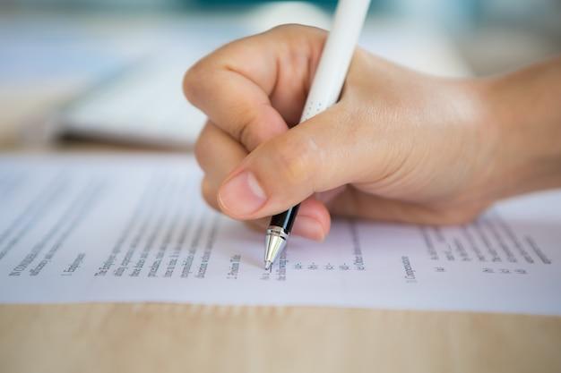 Mão com uma escrita da pena em um papel