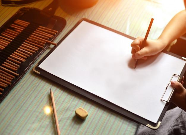 Mão com uma escrita da pena em uma folha em branco