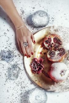 Mão com uma manicure vermelha e uma bandeja de romã