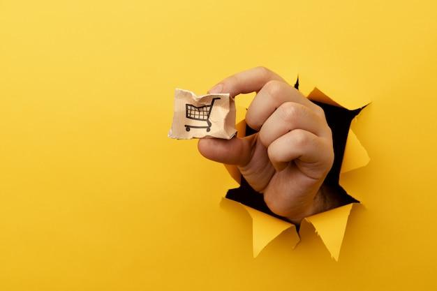 Mão com uma pequena caixa de entrega quebrada através de um orifício de papel amarelo.