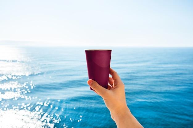 Mão com uma xícara de café em uma mesa de mar azul.