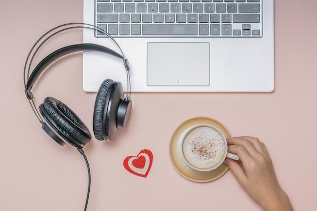 Mão com uma xícara de café, um laptop e fones de ouvido em um coral. trabalho. freelance.