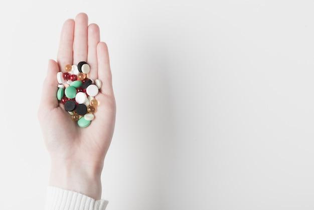 Mão com variedade de pílulas