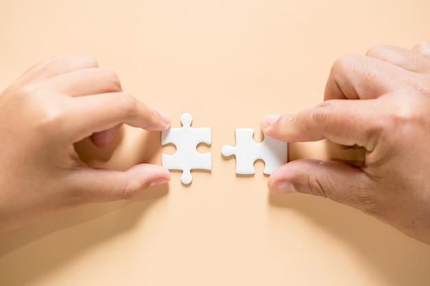 Mão conectando peças de quebra-cabeça na mesa