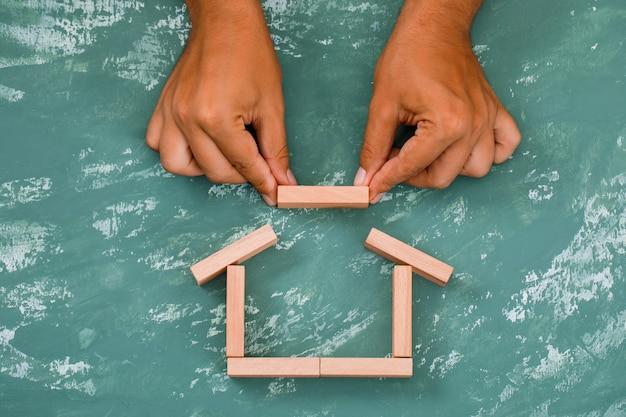 Mão construindo casa com blocos de madeira.