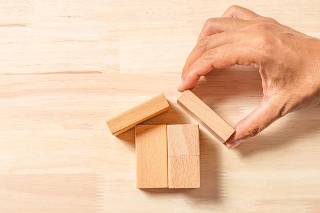 Mão construindo casa com blocos de madeira