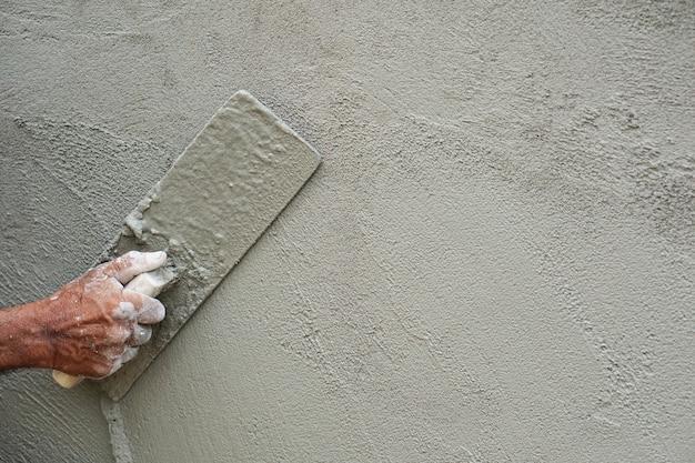 Mão-construtor mão alisando argamassa aplicada na parede