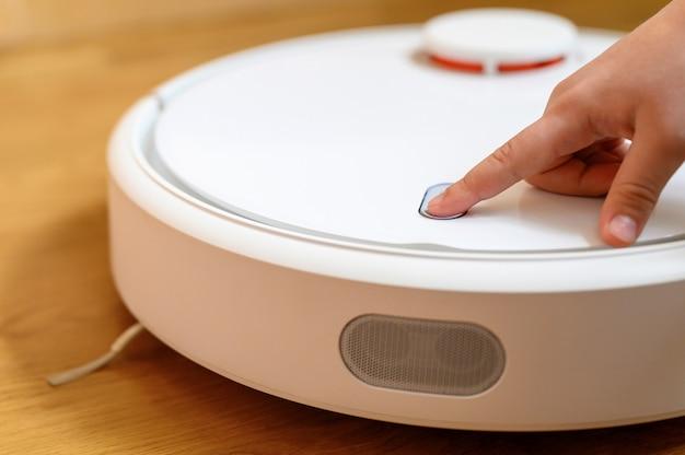 Mão crianças pressiona o botão para ligar o aspirador de pó robô. limpeza doméstica