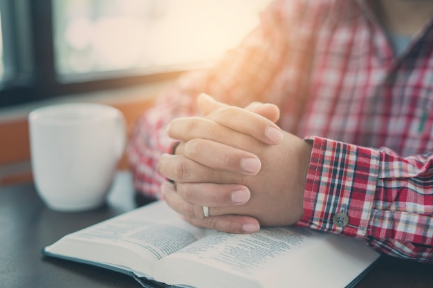 Mão cristã enquanto orava e adorava a religião cristã com fundo desfocado do corpo dela, homem casual orando com as mãos juntas sobre uma bíblia fechada. fundo cristão. liberdade.