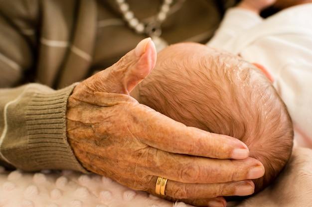 Mão da avó de pele áspera e velha acariciando a cabeça de seu neto recém-nascido