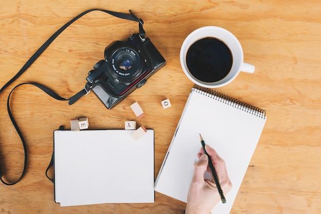 Mão da colheita que escreve no caderno perto da câmera e do café