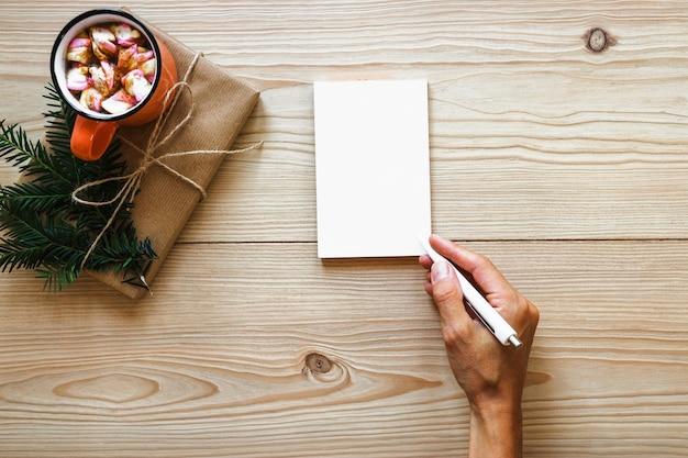 Mão da colheita que escreve no caderno perto do presente e da bebida