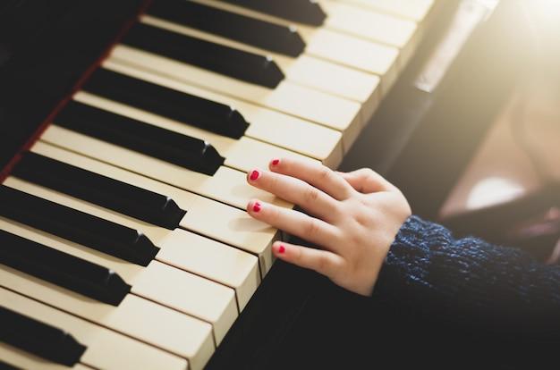 Mão da criança da menina que joga o piano.